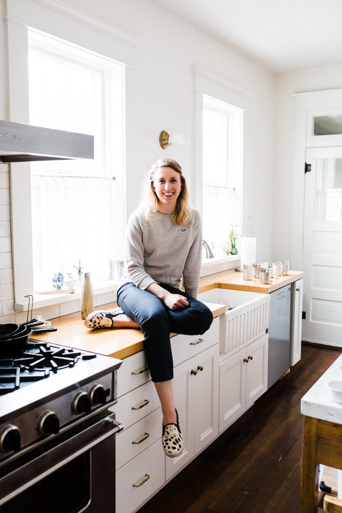 woman sitting on countertop in kitchen