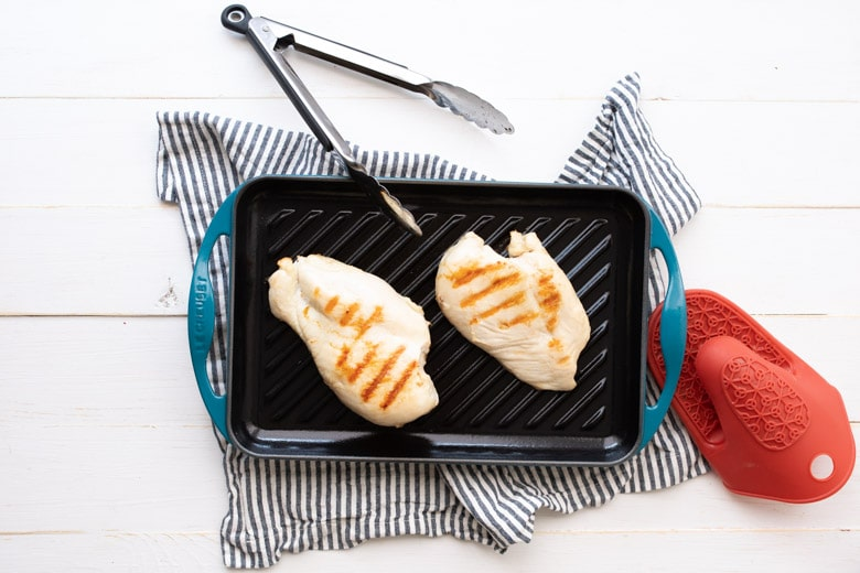 chicken breasts on the grill for grilled chicken burger