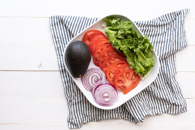 avocado, red onions, tomato slices, and lettuce leaves on a plate