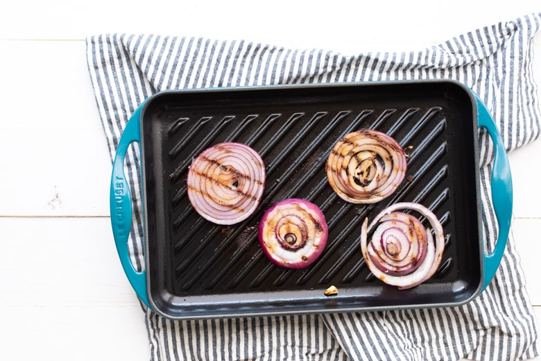 red onions on the grill for grilled chicken burger
