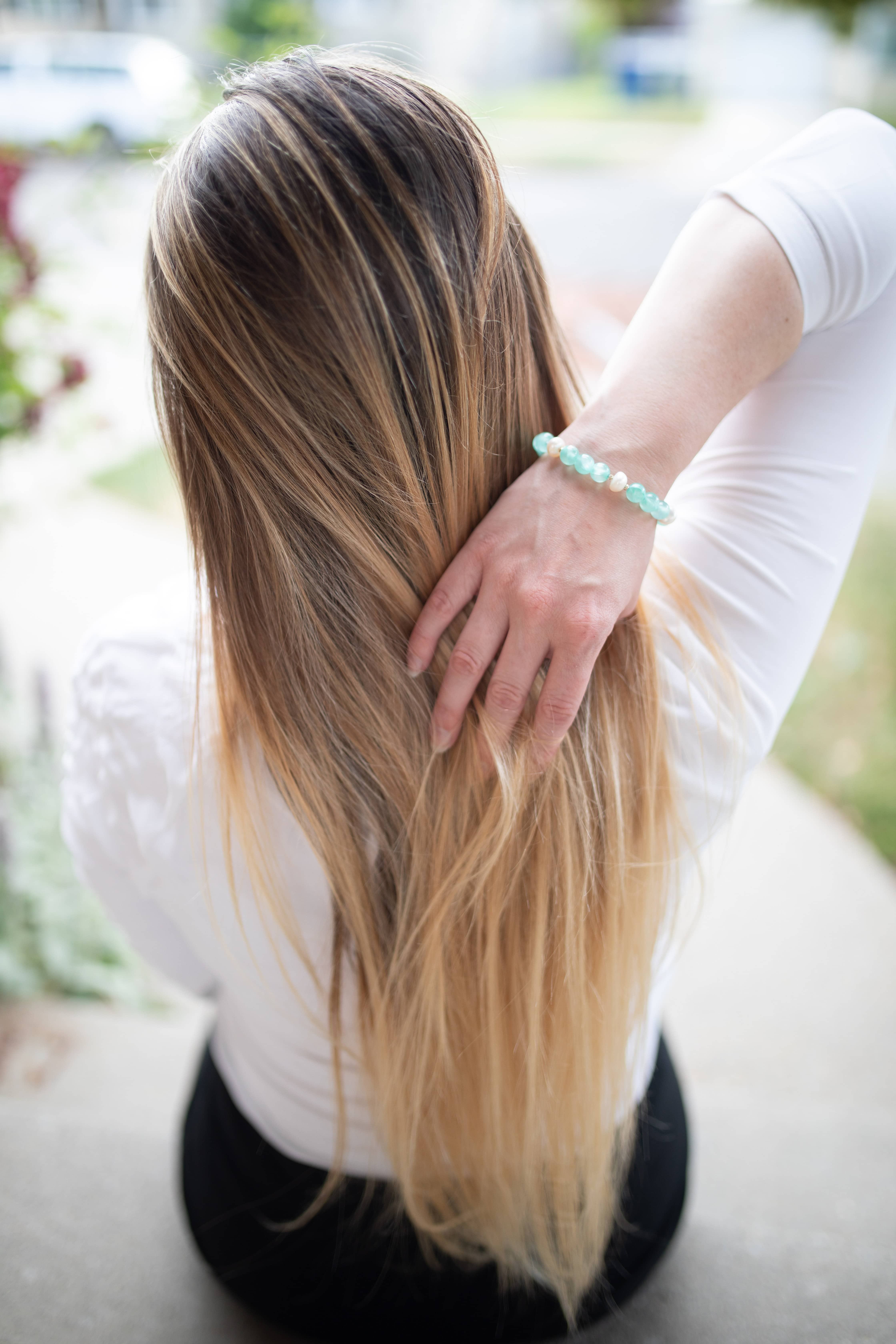woman running her hand through the back of her hair
