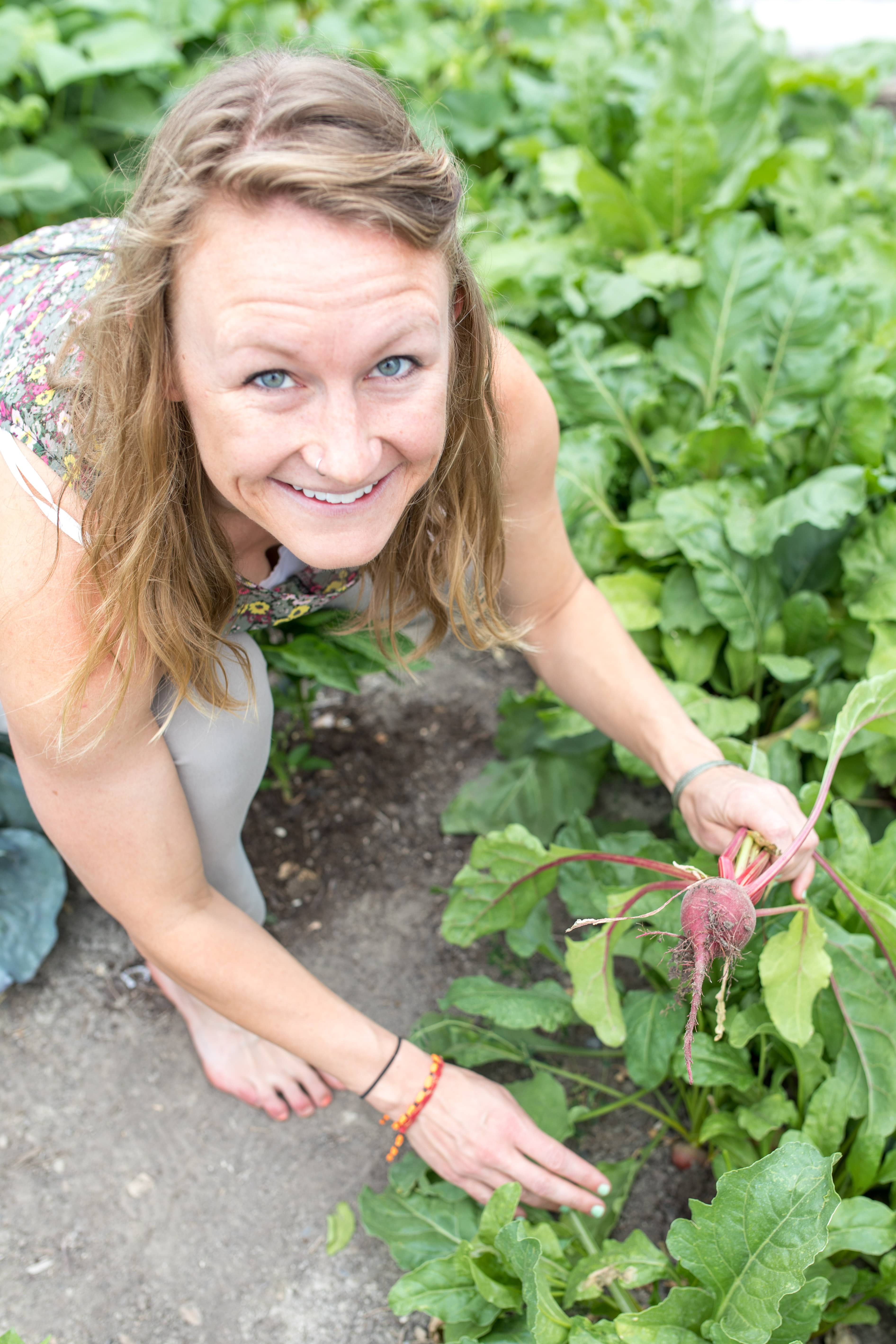 woman in garden holding beets