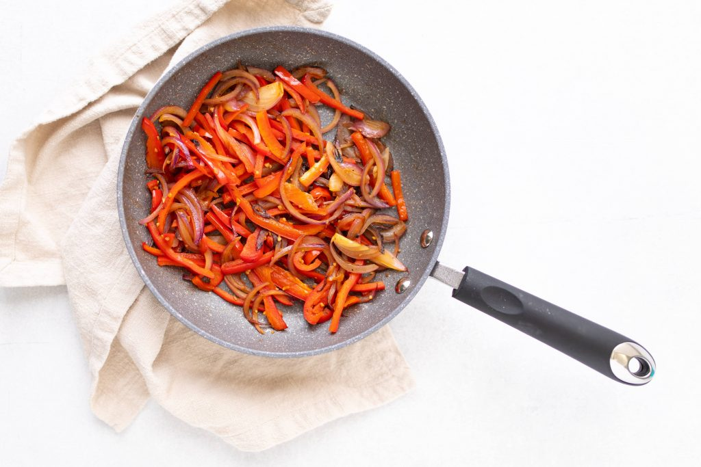 red bell pepper and onions in sautee pan for black bean and vegetable quesadilla