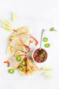 black bean & vegetable quesadilla on table with salsa and toppings