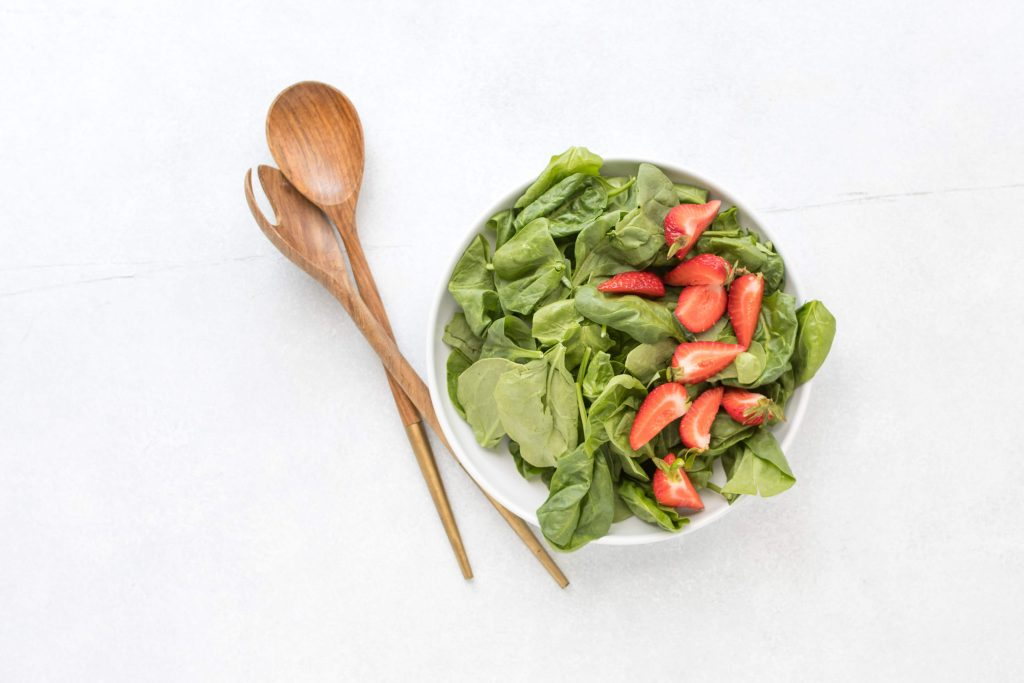 spinach and strawberries in bowl for summer berry salad