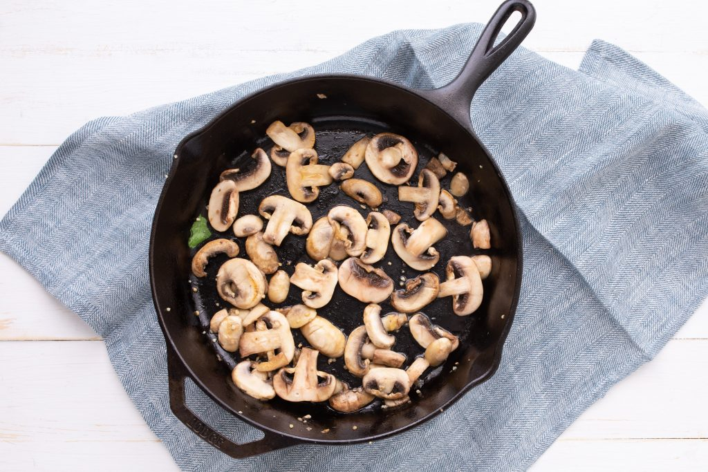 mushrooms in a cast iron skillet for easy tortellini with sausage recipe