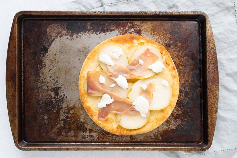 pears, prosciutto, and goat cheese cooked on a pita on top of a small baking sheet