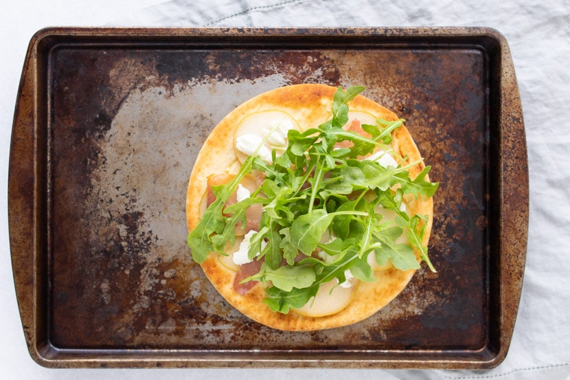 cooked pear prosciutto and arugula flatbread on pan