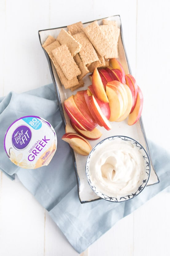 PB Greek yogurt dip with Dannon Light & Fit yogurt cup, apples, and graham crackers on table