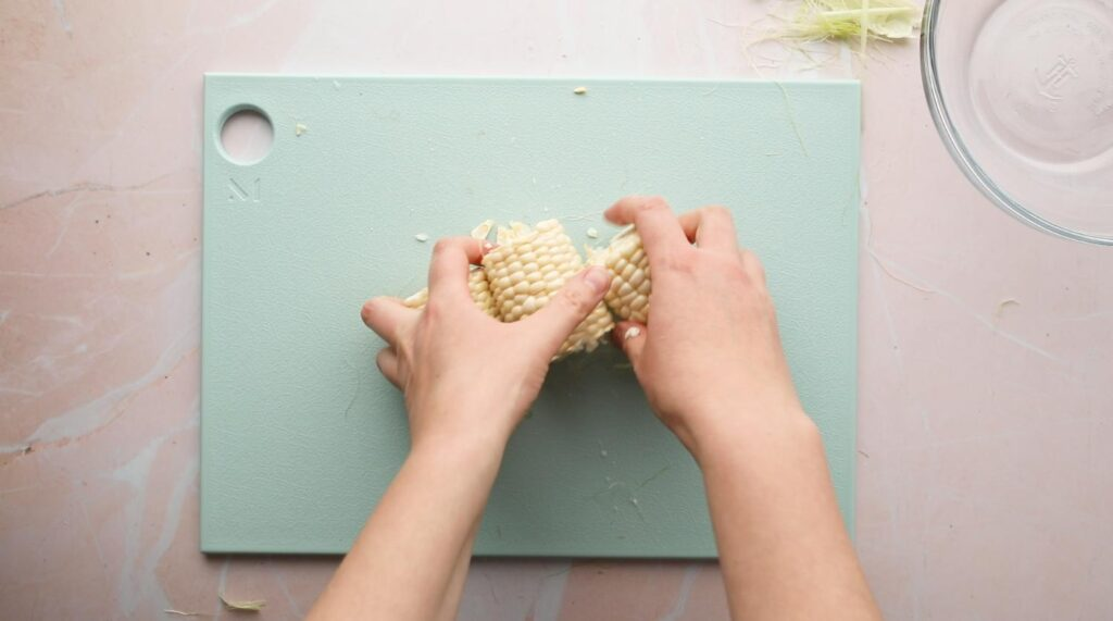 hands holding pieces of an ear of corn on a cutting board