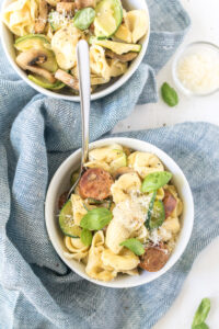 sausage and artichoke tortellini in bowl with garnishes on table
