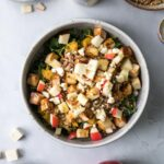 warm harvest bowl with apples and maple glazed butternut squash with wild rice and barley on table