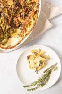 rustic potato and brussels sprouts au gratin on plate with pan on table