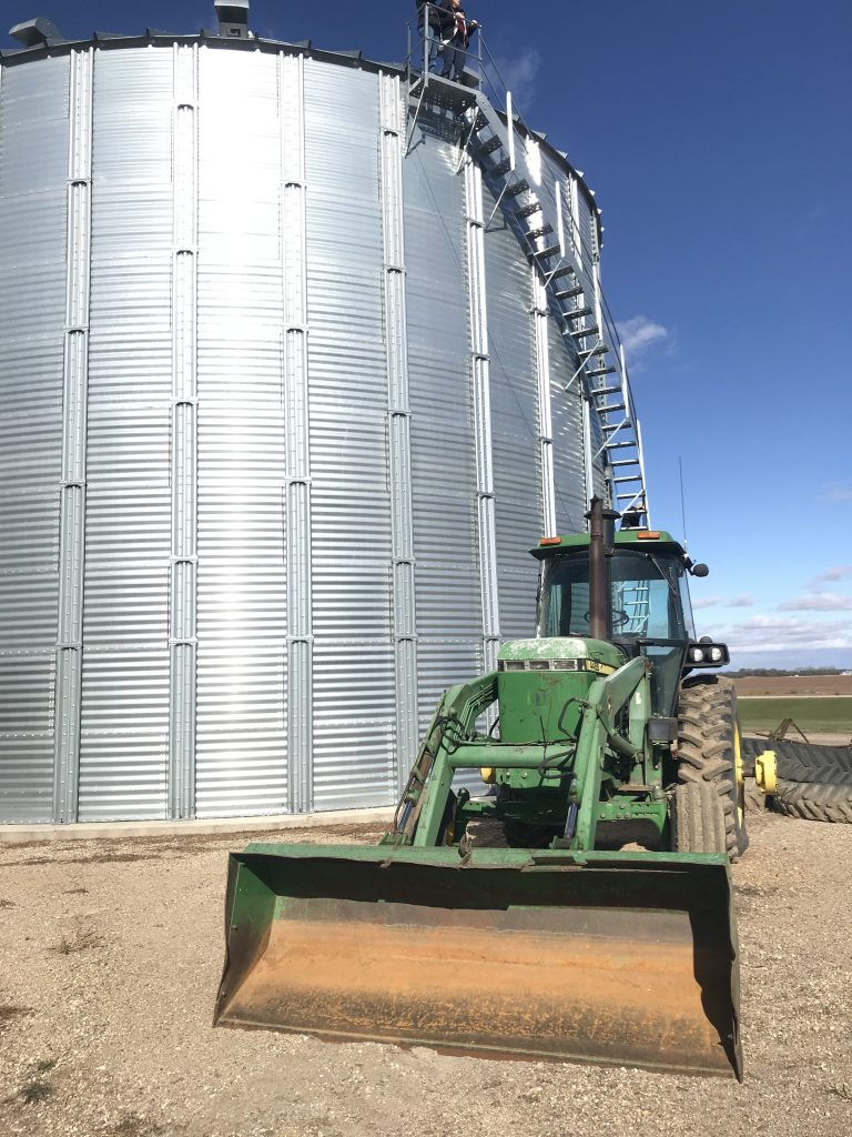 green tractor in front of a soybean silo in North Dakota
