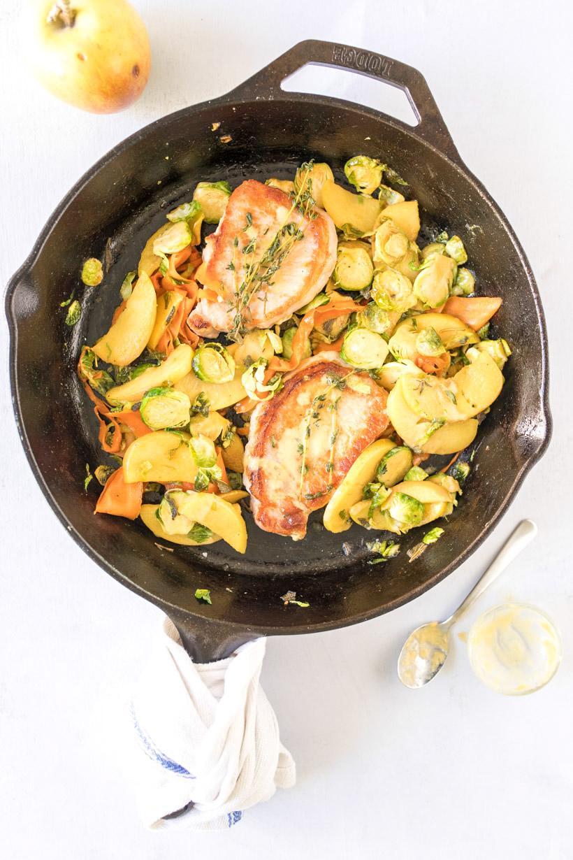 two pork chops, apples, carrots, and brussels sprouts in a cast iron skillet