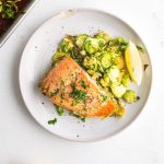 maple mustard salmon and brussels sprouts with a lemon wedge on a plate