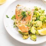 maple mustard salmon and brussels sprouts with a lemon wedge on a white plate