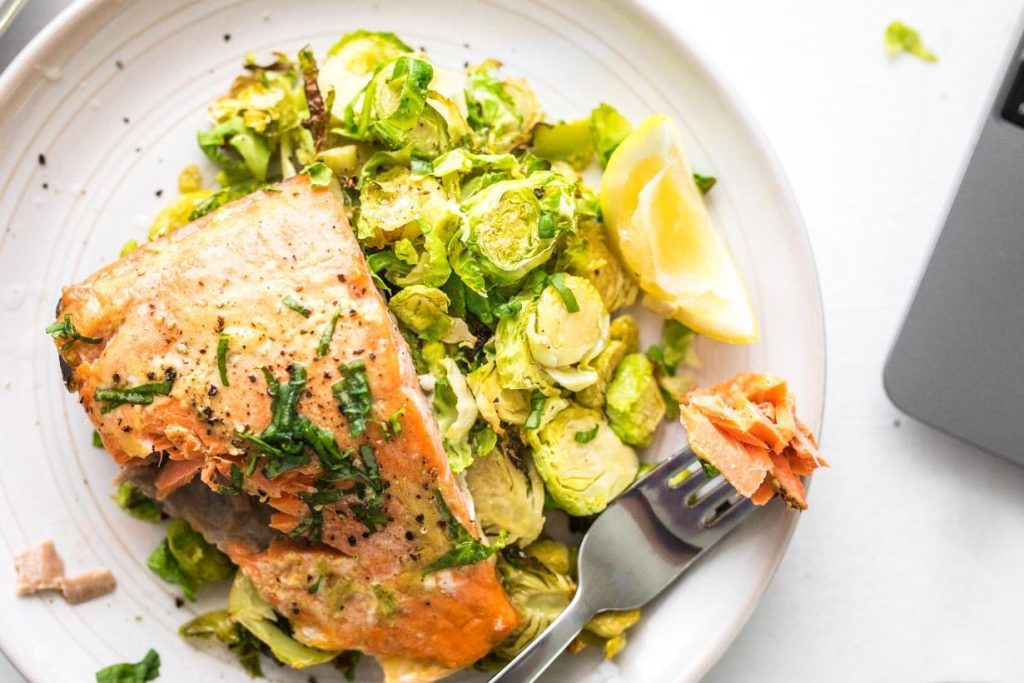 fork with maple mustard salmon on brussels sprouts with a lemon wedge on a white plate