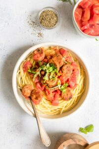 simple pasta in a white bowl with ingredients surrounding it