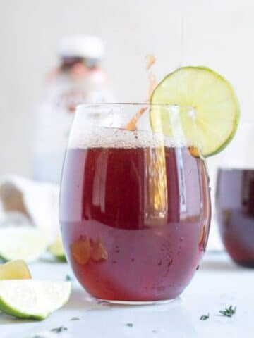 cherry drink in a glass with a lime slice on the rim