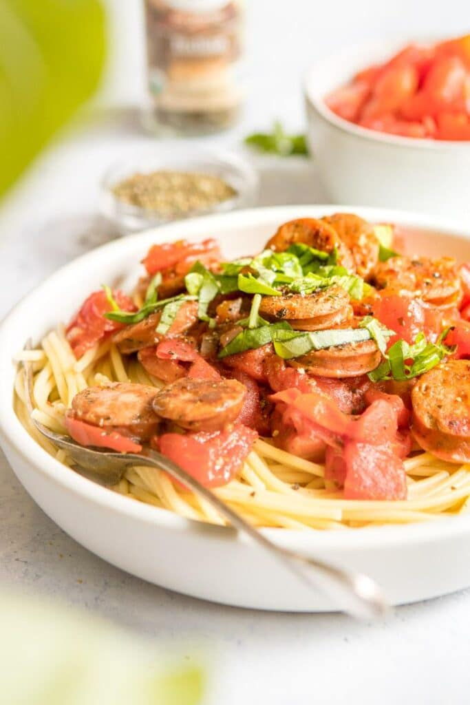 simple pasta in a white bowl with sausage on top and ingredients behind