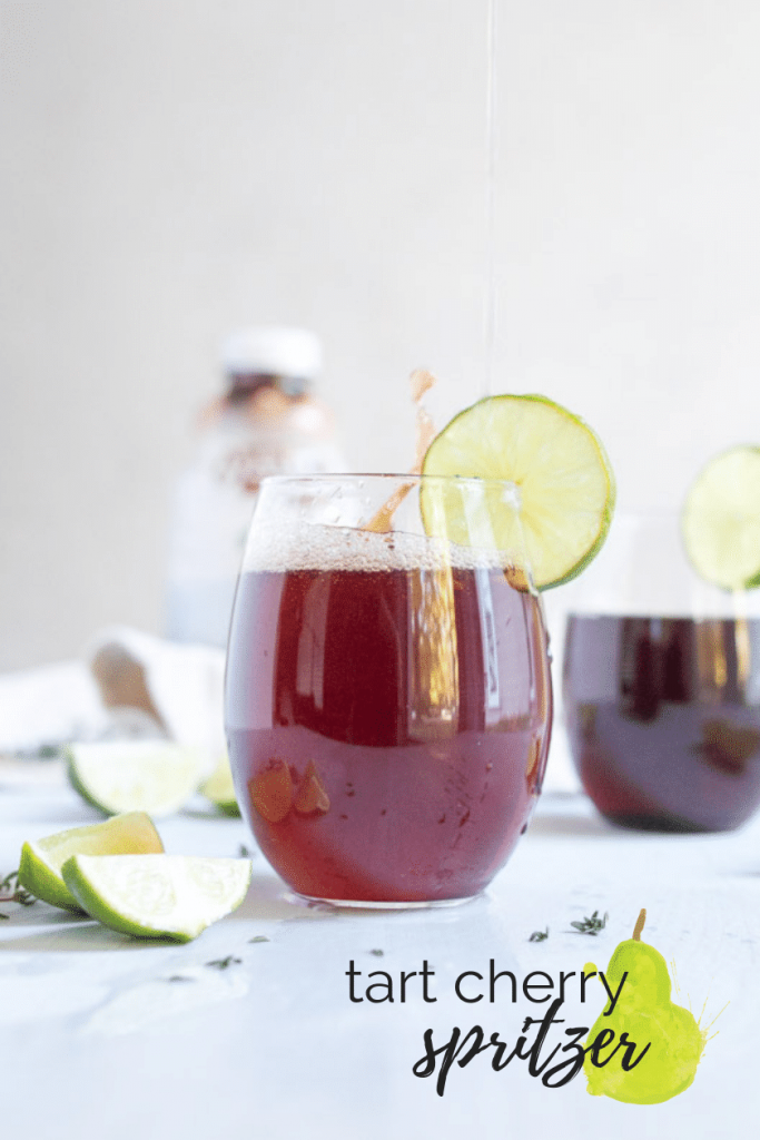 tart cherry spritzer in cup with limes on table with text overlay