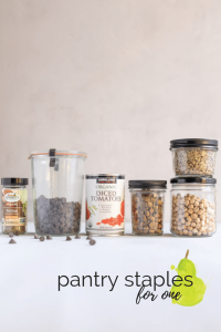 pantry staples for one: canned goods, chocolate chips, and grains in jars on a table