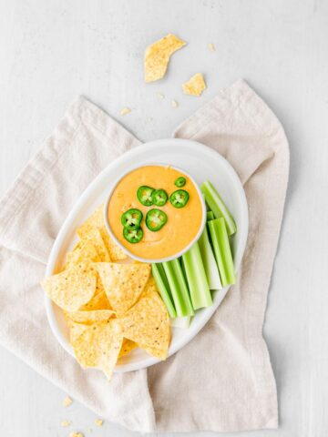 easy queso dip with chips and celery on a plate