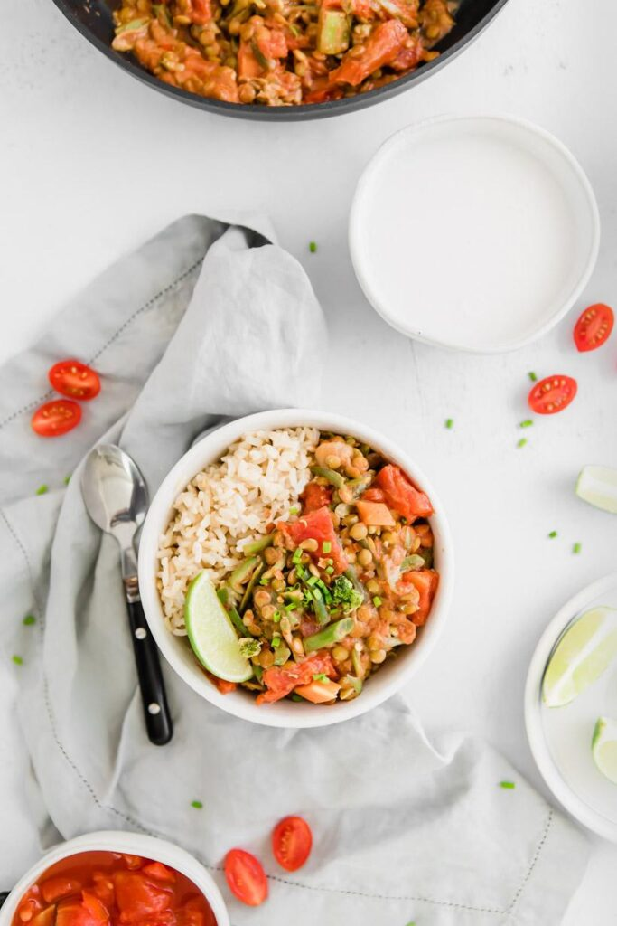 green lentil coconut curry on table with ingredients