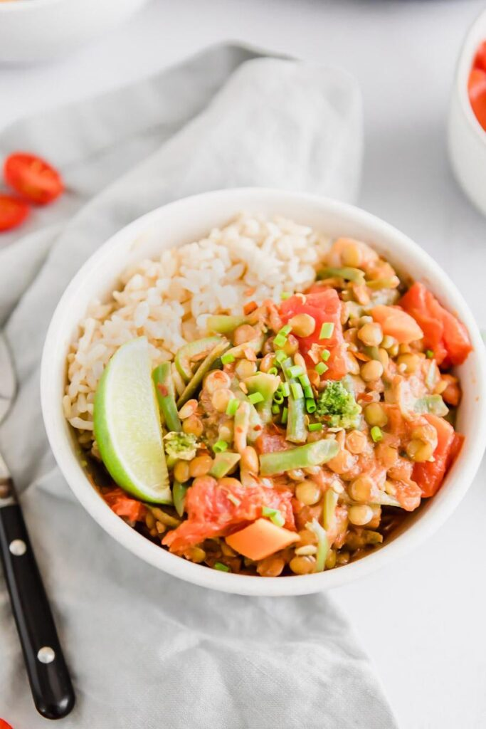 close up of green lentil coconut curry in a bowl