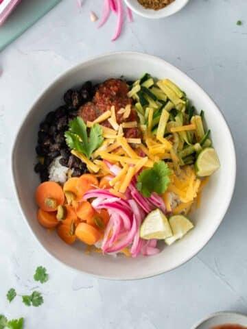 square image of burrito bowl with veggies on top