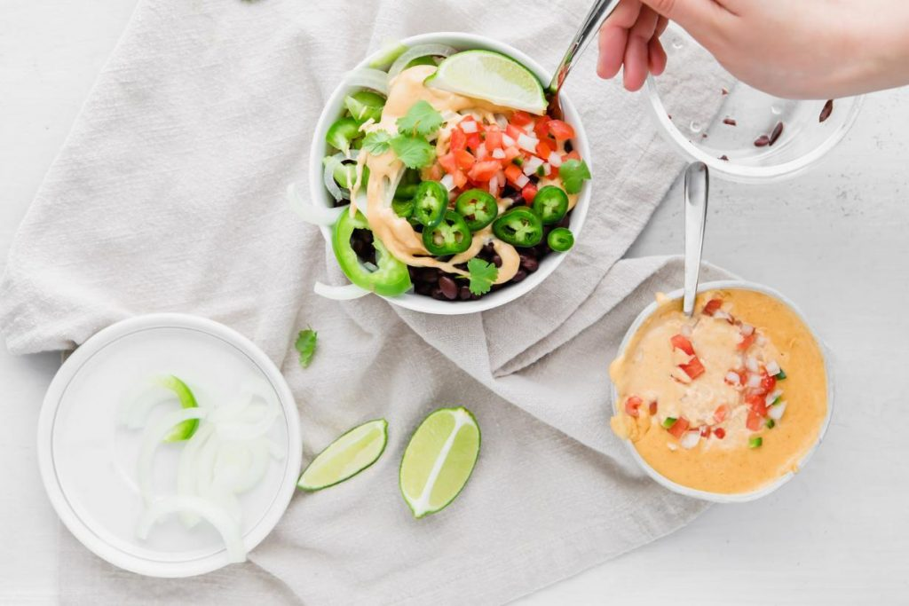 vegetarian burrito bowl recipe with queso in a bowl with other ingredients on a table