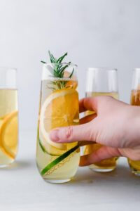 holding an apple mocktail in a stemless champagne glass with citrus and rosemary