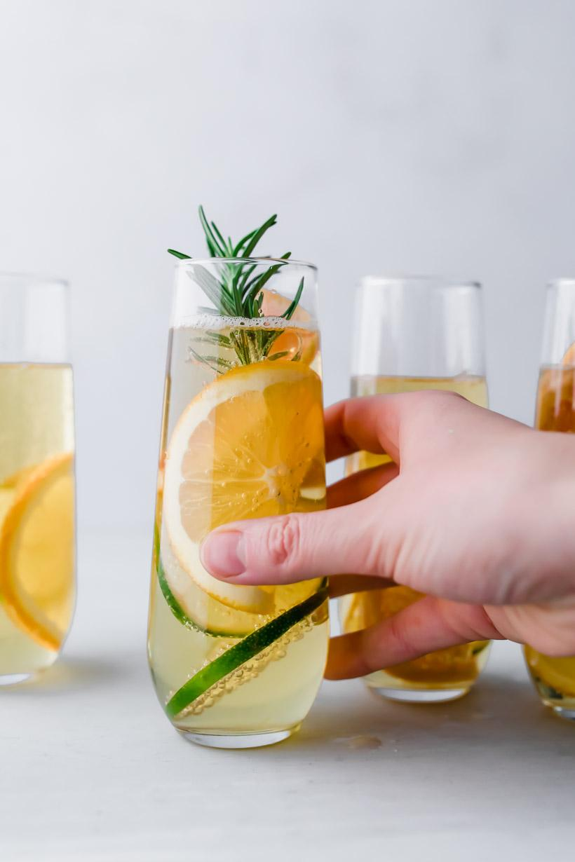 holding an apple mocktail with sliced citrus and rosemary in a stemless champagne glass