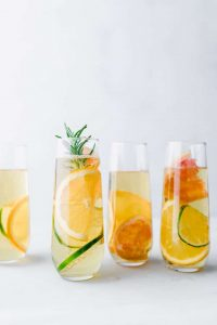 apple mocktails in stemless champagne glasses with citrus and rosemary