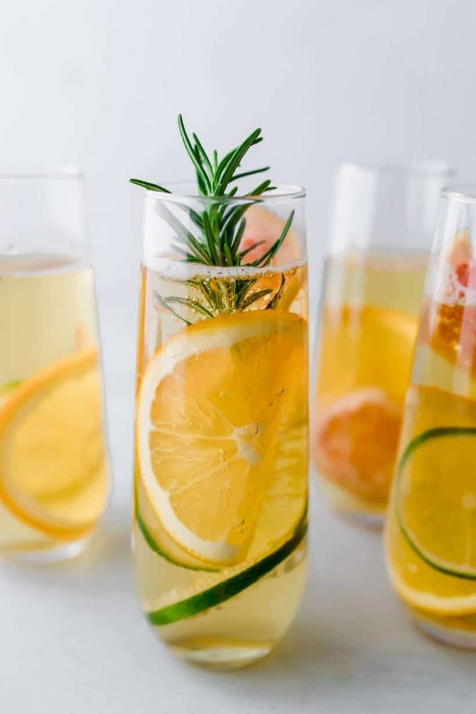four apple mocktails in stemless champagne glasses with citrus and rosemary