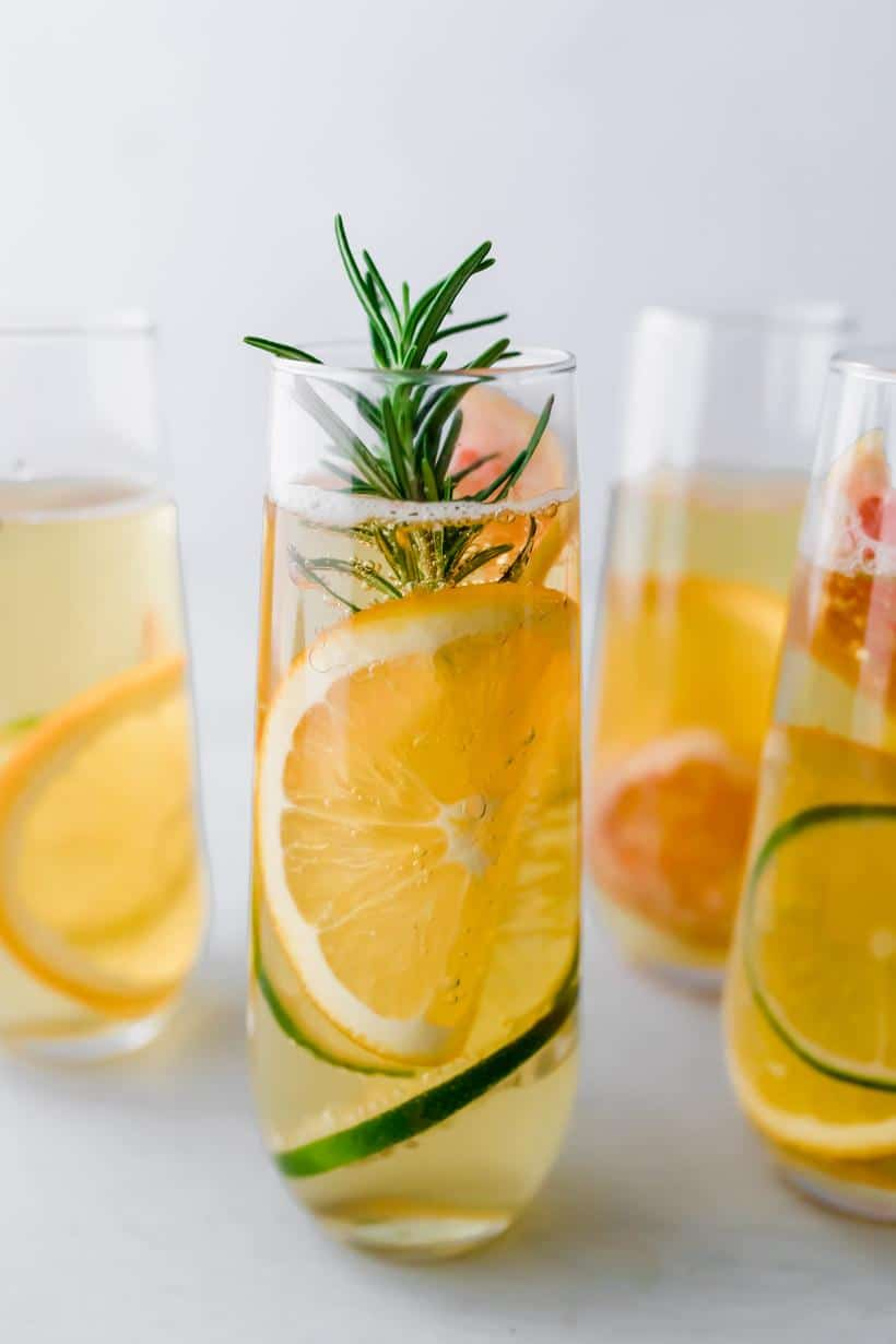 four apple mocktails in stemless champagne glasses with thin slices of citrus and rosemary in each glass