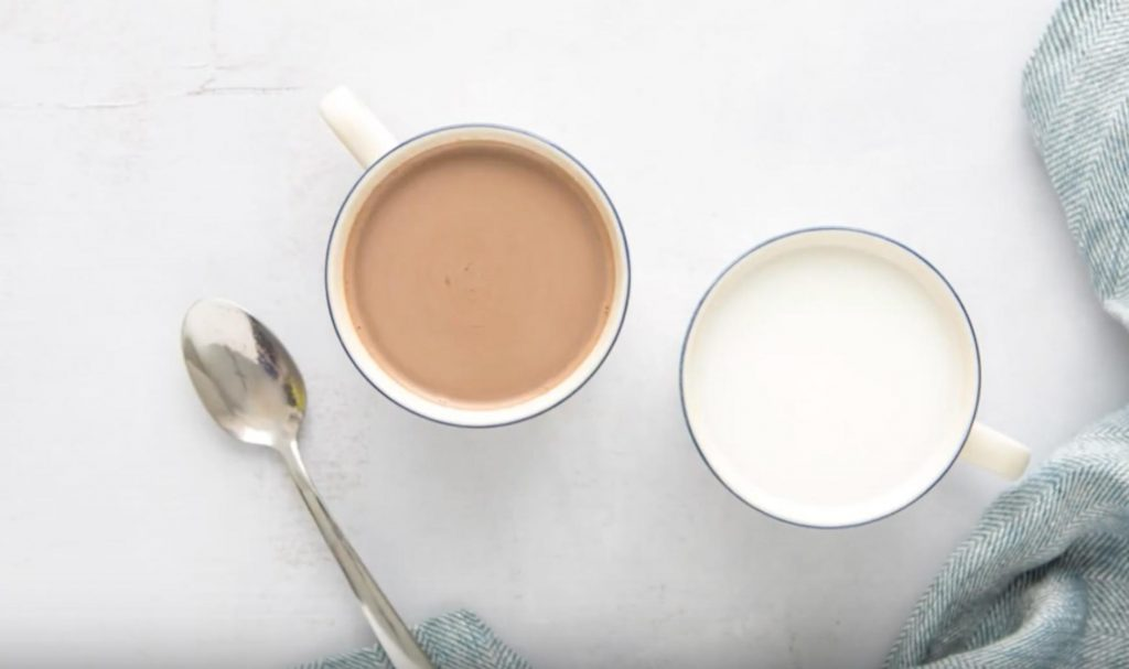 two mugs, one with hot cocoa, the other with milk next to a spoon