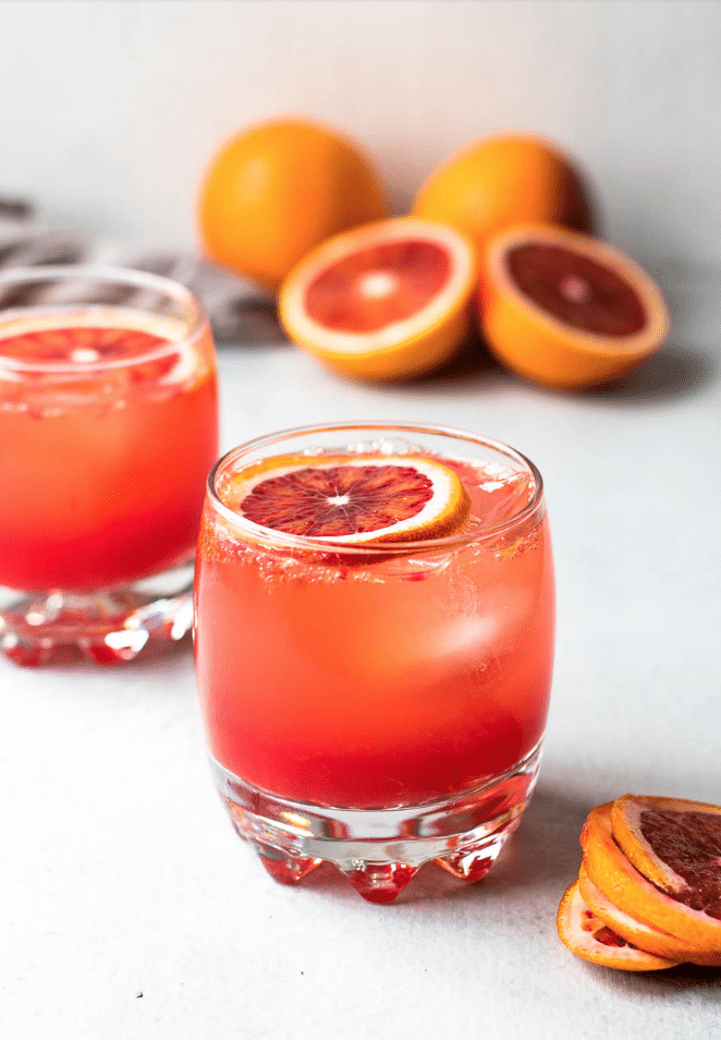 blood orange drink with a slice of blood orange on top with oranges in background