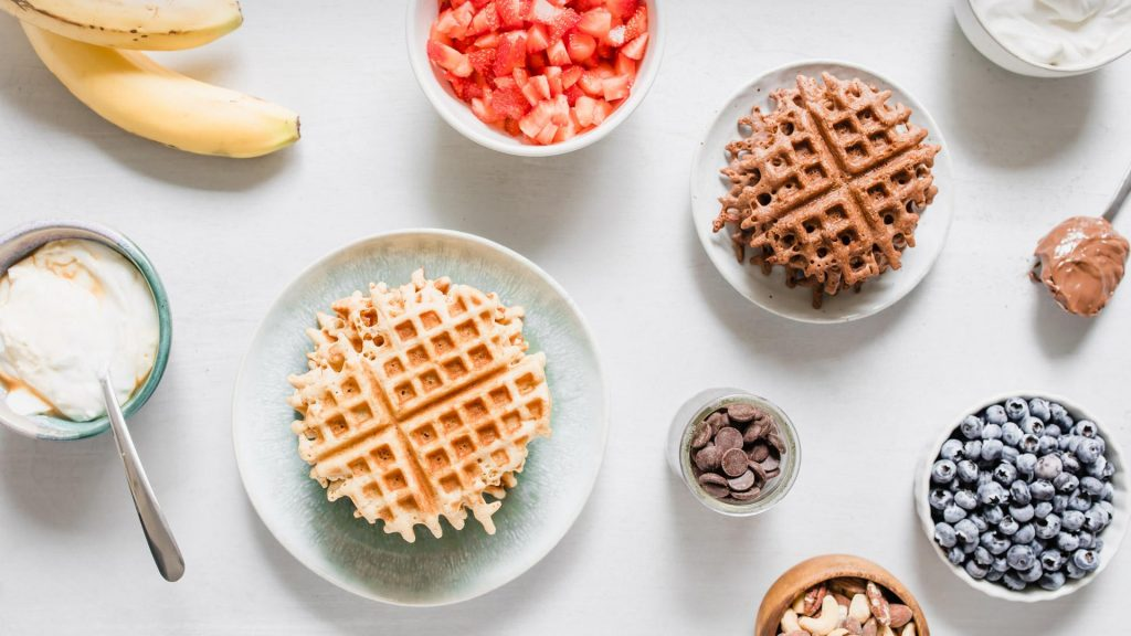 Waffles and waffle toppings in individual dishes on a table for a DIY waffle bar