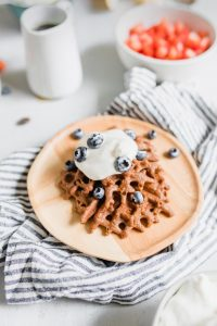 chocolate waffle with whipped cream and blueberries on a plate for a DIY waffle bar