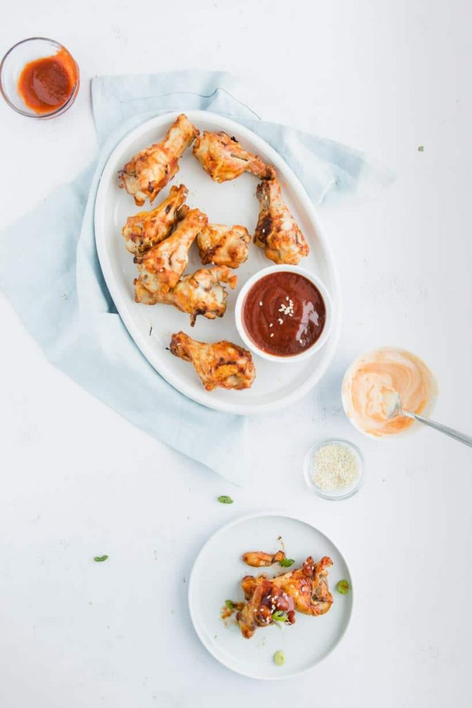Asian BBQ Chicken Wings Recipe on a table with dipping sauces