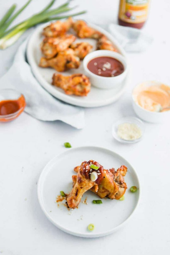 Asian BBQ Chicken Wings on a plate with more in background