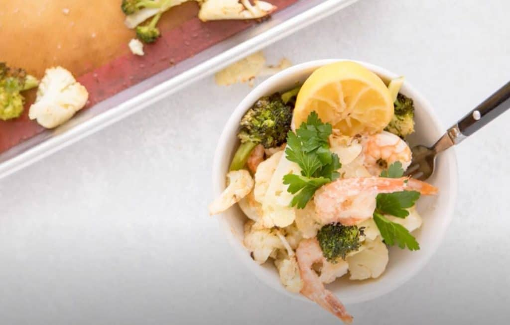 shrimp, broccoli, and a lemon wedge in a bowl