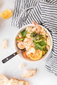 shrimp sheet pan dinner in a bowl with bread on the side