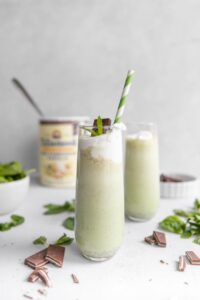 homemade shamrock shake with green straw and ingredients in the background