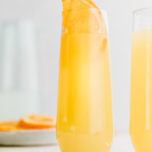 mimosa mocktail in a glass with an orange