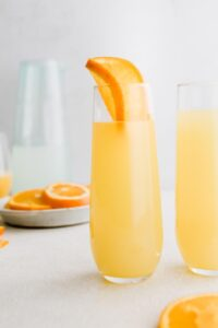 mimosa mocktail in a glass with oranges in background
