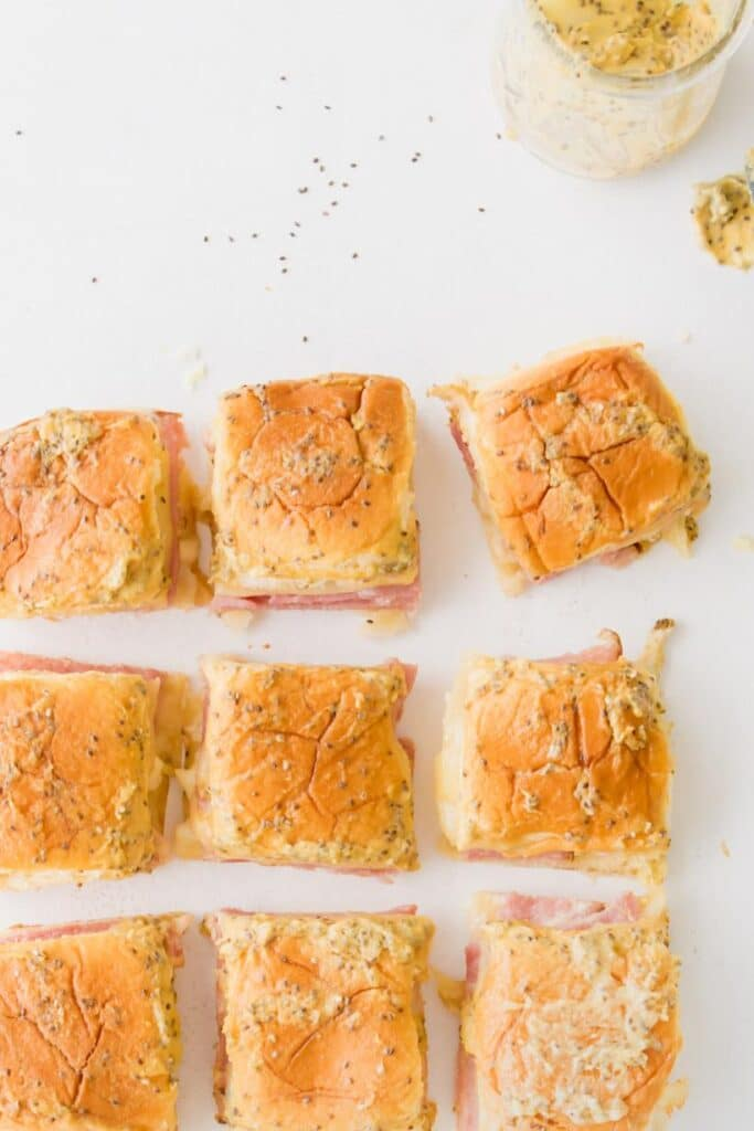 ham and swiss sliders on a table with ingredients surrounding them