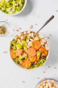 white bean and farro bowl with carrots and leeks in a bowl, with ingredients on table